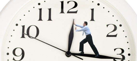 Man standing on big hand of clock and pushing small hand backwords - to slow down time