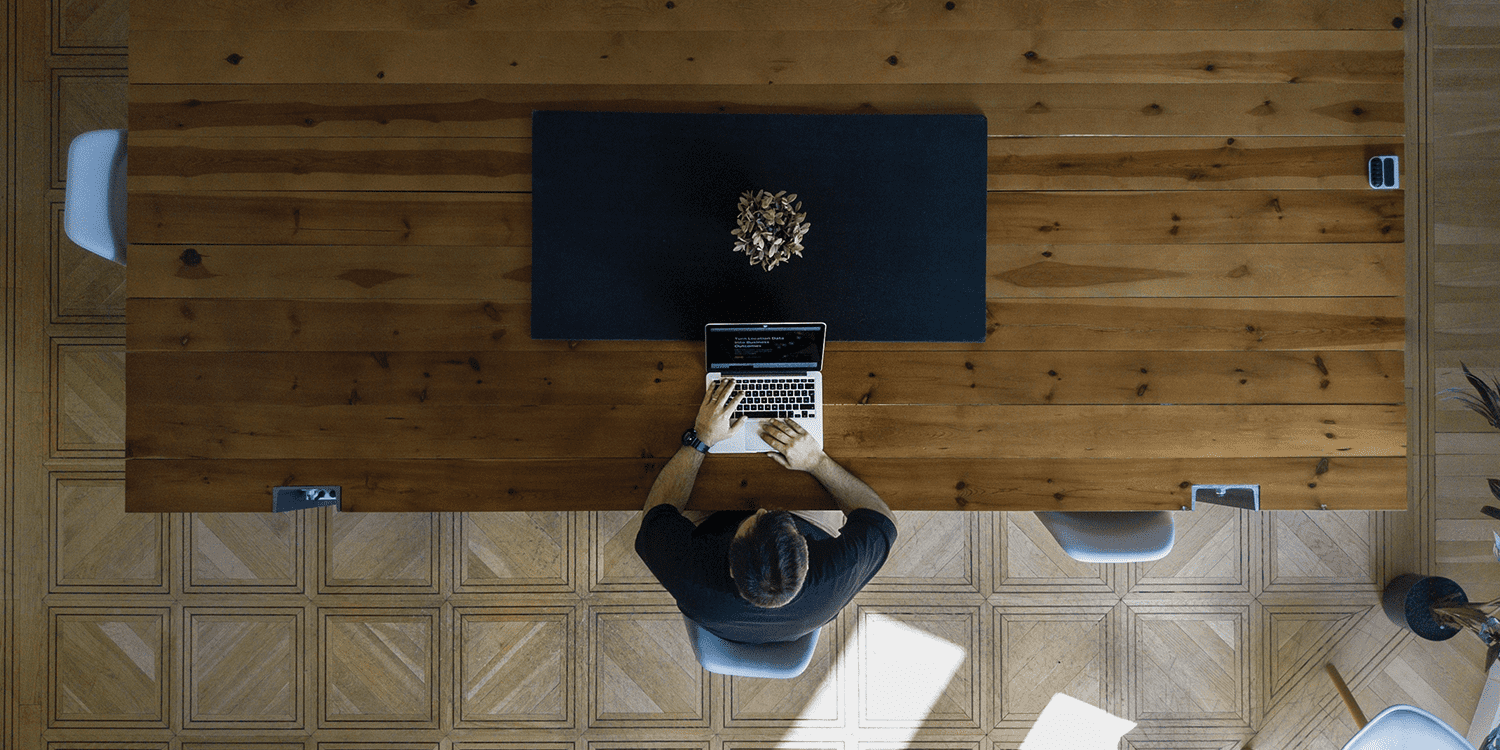 Bird's eye view of a person sitting at a table whilst typing on a laptop, illustrating that you only require one person to form a limited company.