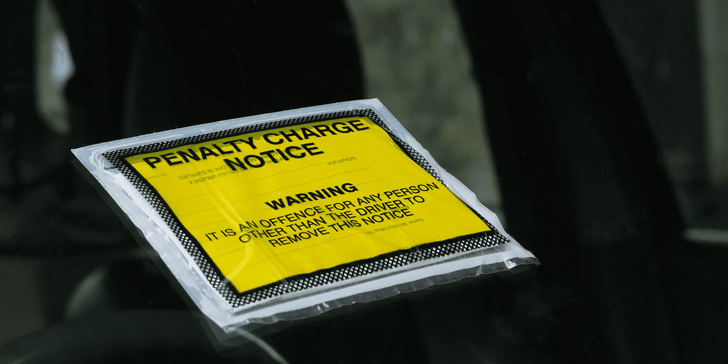 A square, yellow Penalty Charge Notice stuck to the windshield of a car, illustrating the concept of late filing penalties imposed on limited companies.