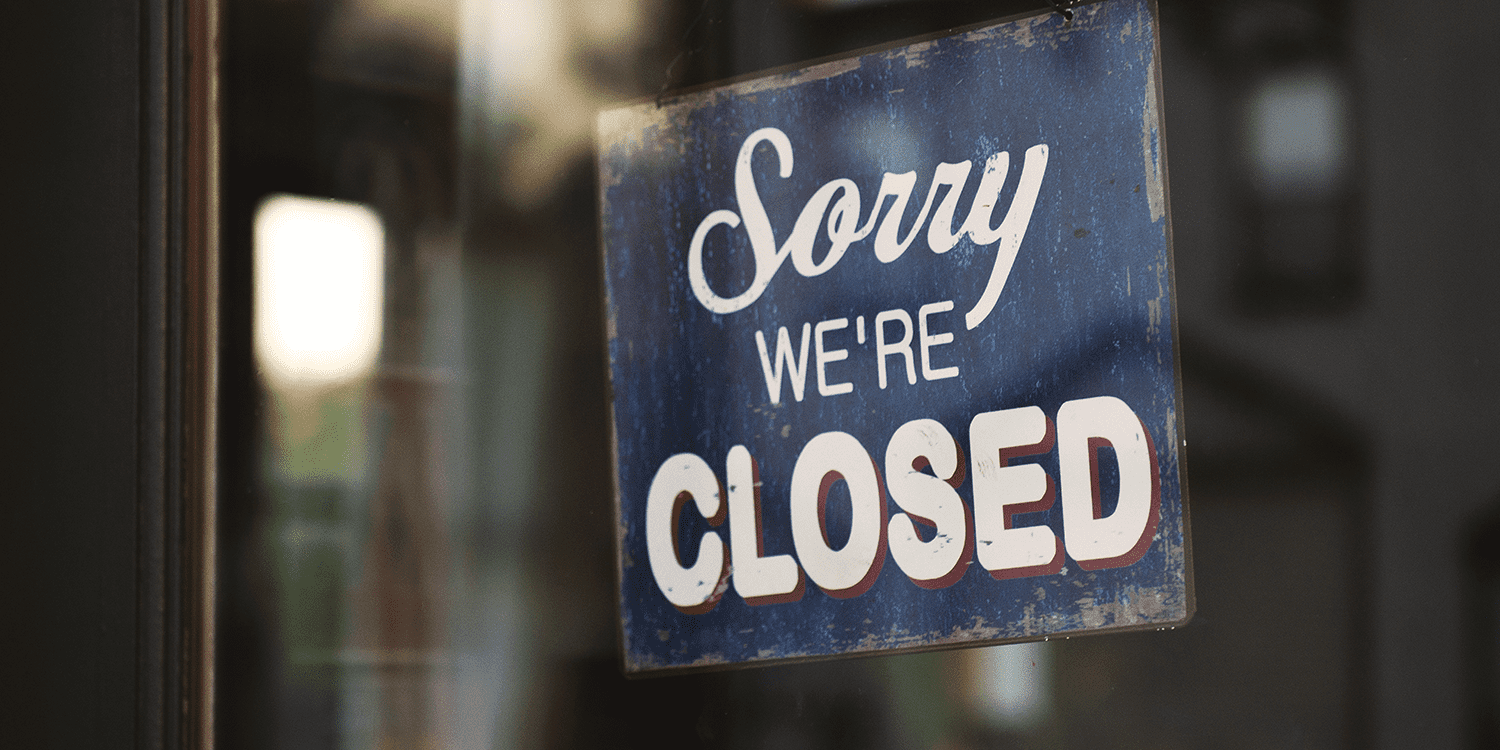 "A sign hanging from a glass-fronted door, displaying the words ""Sorry, we're closed""."