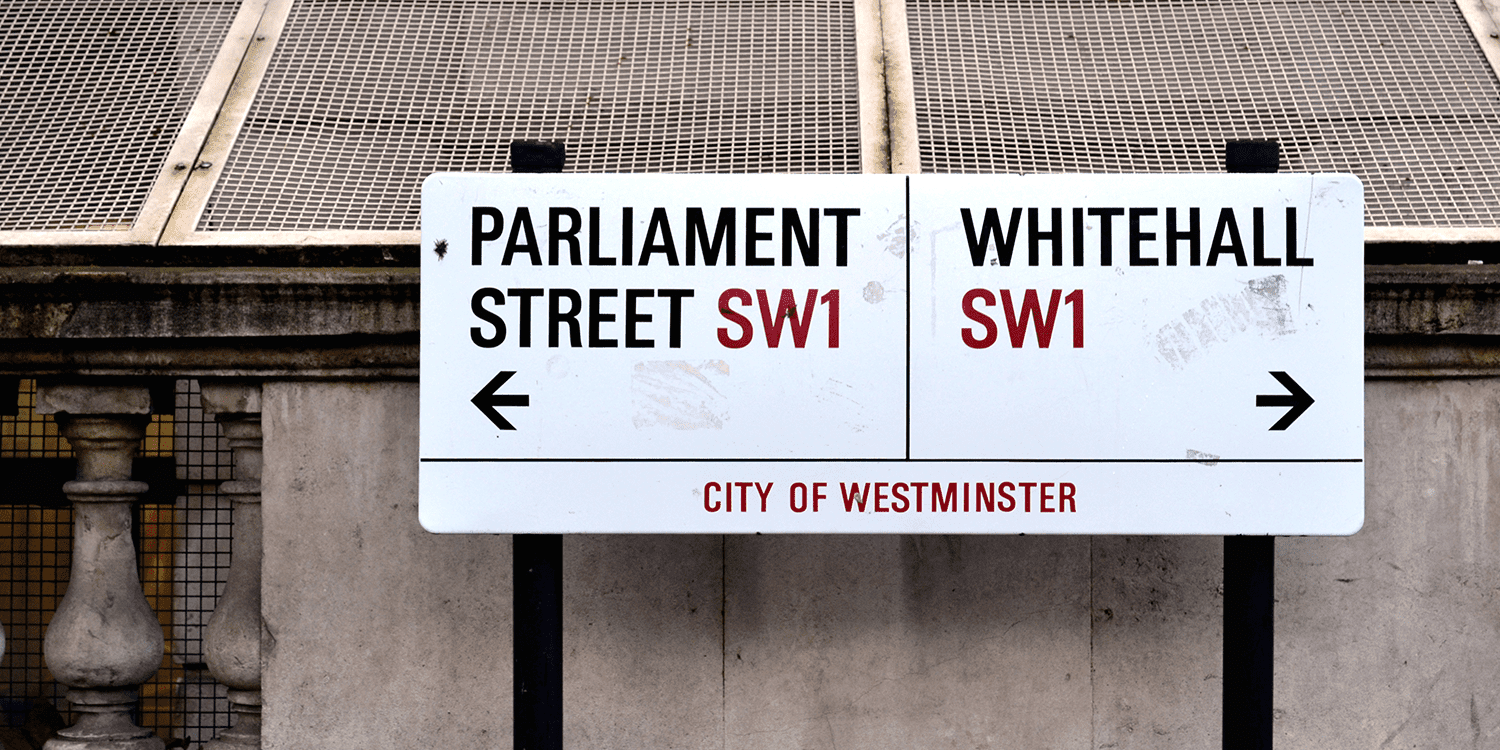 """Image of a white street sign in London, printed with the words """"Parliament Street Sw1, Whitehall SW1, City of Westminster"""", representing our optional registered office service in London."""
