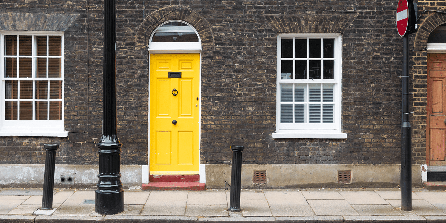 Photograph of a Georgian building with a yellow door, providing an example of the type of physical address you can use as a service address or registered office.