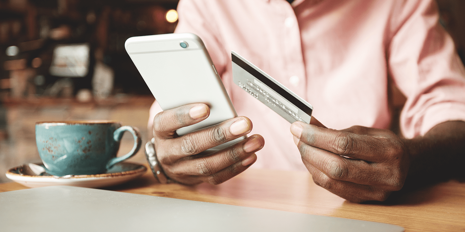 Image of a person holding a mobile phone in one hand and a bank card in the other, illustrating the ease of setting up a business bank account for a limited company and managing finances online.