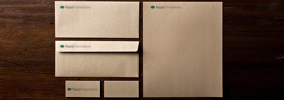 A set of blank business stationary featuring the Rapid Formations logo, sitting neatly on top of a mahogany desk.