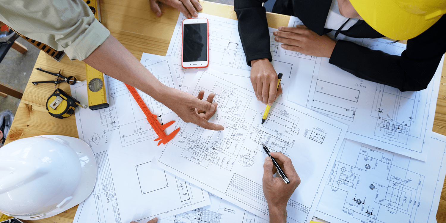Image of quantity surveyors, who often work as contractors, reading floor plans and blueprints on a large desk