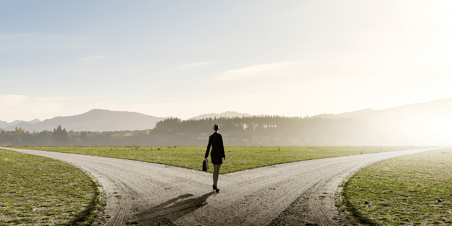 Woman standing in front of two roads that veer off in different directions, illustrating the choice of Limited or Ltd at the end of a company name.