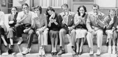 A vintage black-and-white photographic featuring a group of well-dressed young people eating ice cream outisde on the steps of a building.