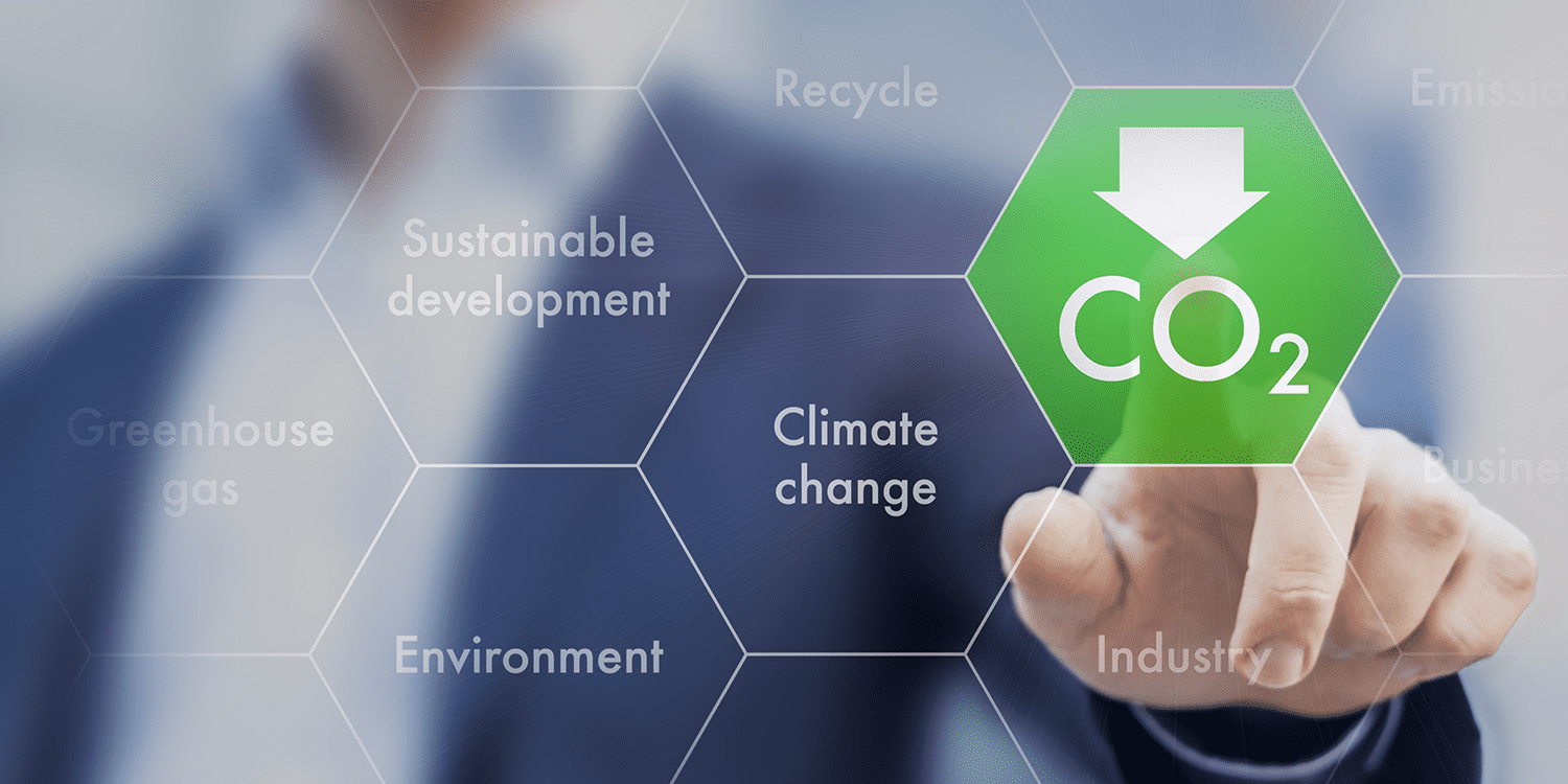 Image of a man in a suit placing his finger on a green hexagon that contains chemical formula CO2.