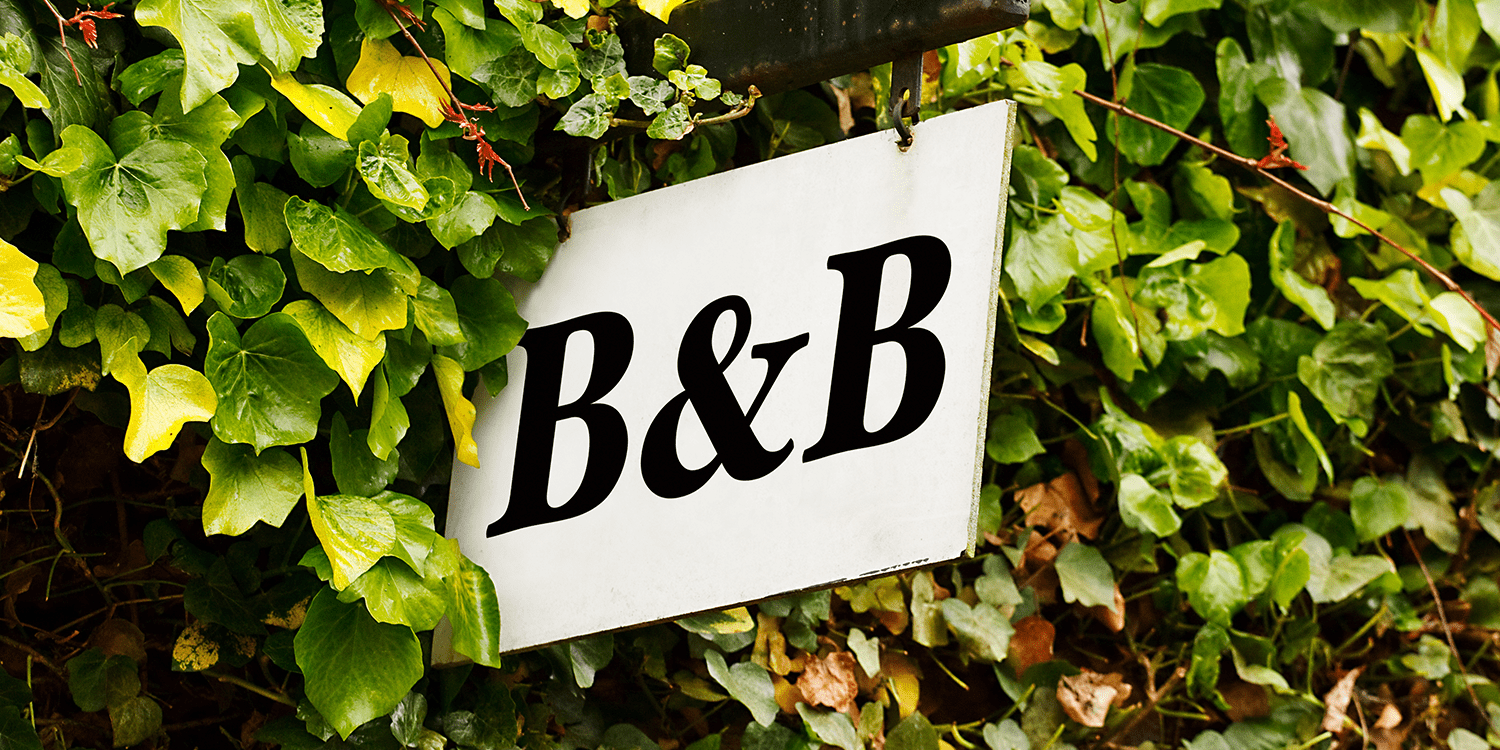 Image of a B&B sign protruding from an ivy-covered wall, illustrating the concept of starting a bed and breakfast business in the UK.