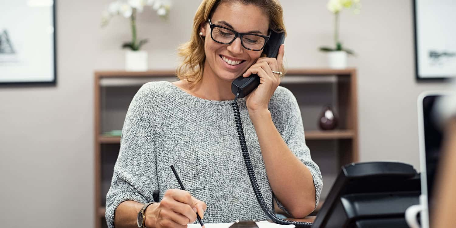 Image of a woman holding a telephone handset to her ear whilst sitting at her desk, illustrating the concept of a business landline telephone number.