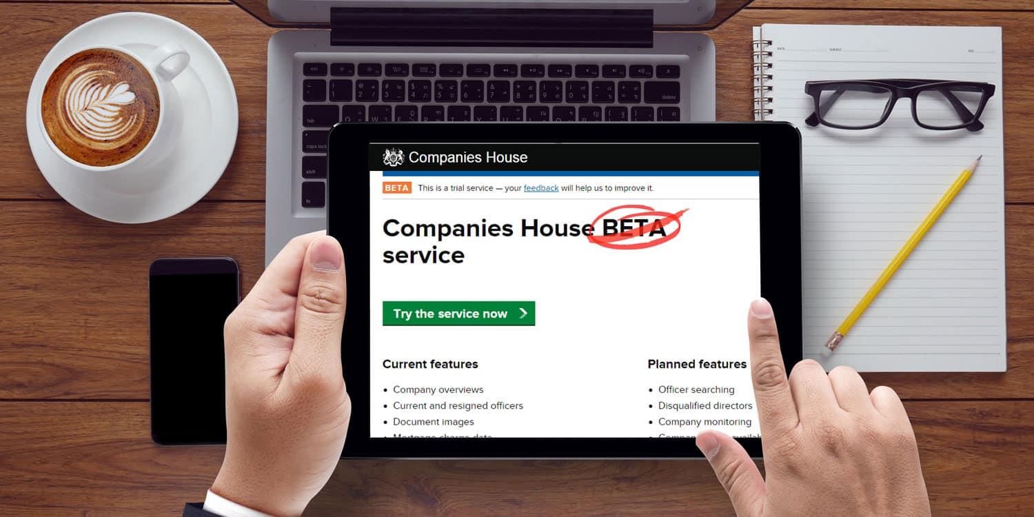 A business person holding an iPad displaying the new Company House Service with the old 'BETA' name scored out.