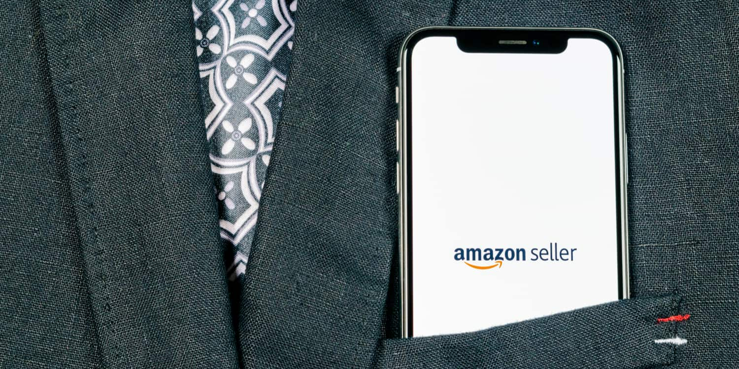 "Close-up of a mobile phone protruding from the chest pocket of a suit jacket, with ""Amazon seller"" displayed on the screen, illustrating the concept of choosing to sell on Amazon."