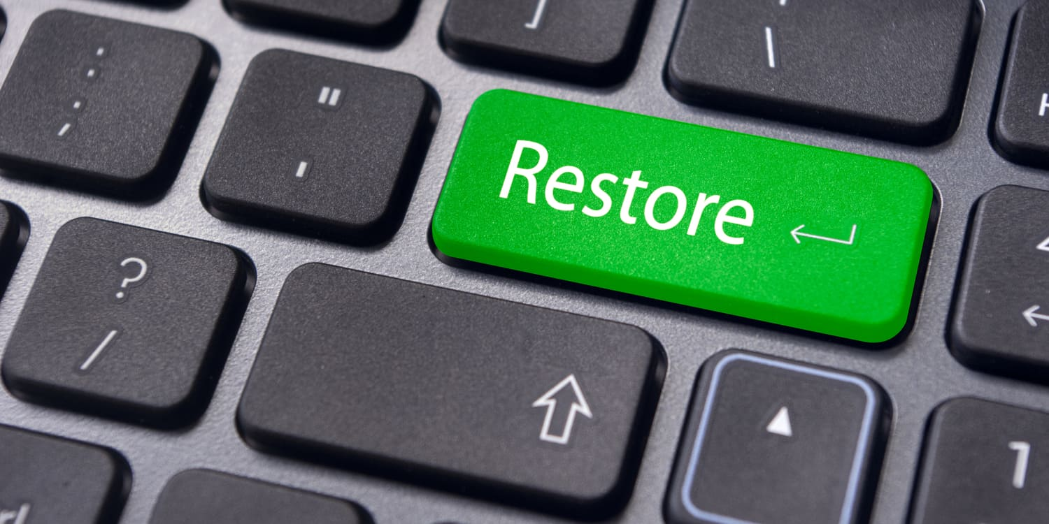 A close up of a laptop keyboard with one green key labelled 'Restore', representing the concept of applying to restore a company
