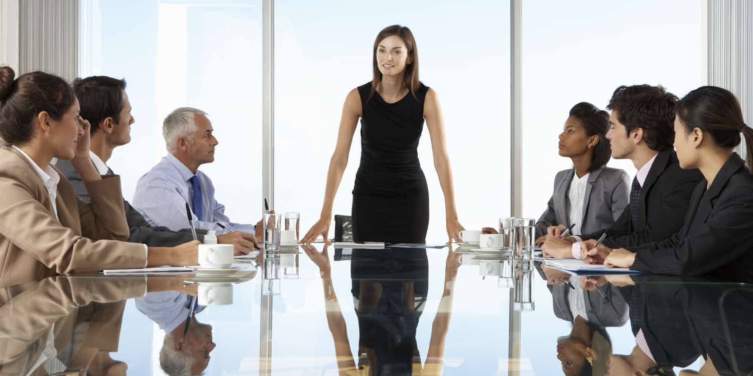 Photograph of a group of business men and women sitting around a large boardroom table, illustrating the concept of limited company meetings and resolutions