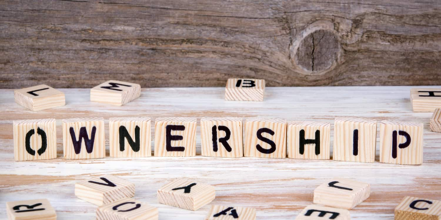 Wood blocks sitting on a table, displaying the word 'OWNERSHIP', illustrating the query pertaining to who owns a limited company.