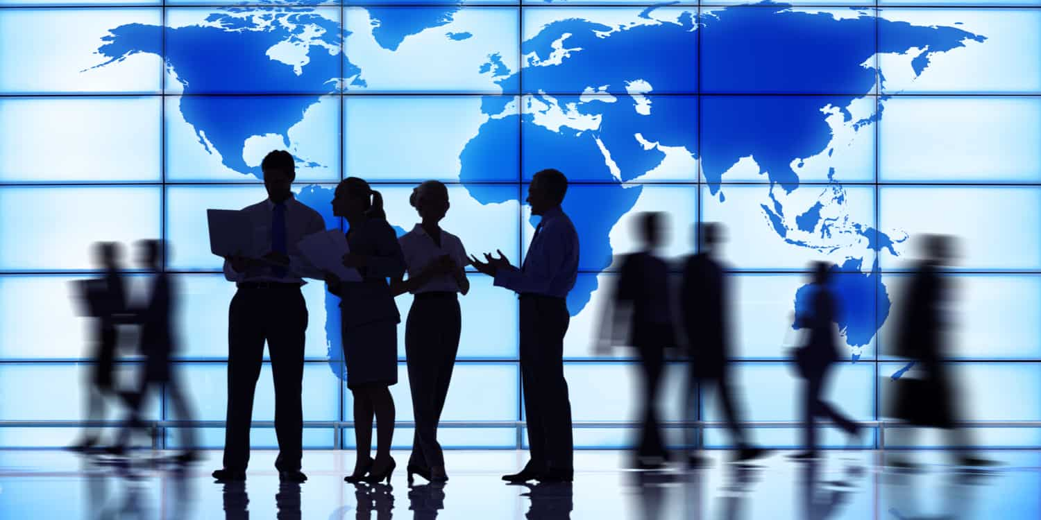Business people silhouetted against a large glass wall displaying a map of the world.