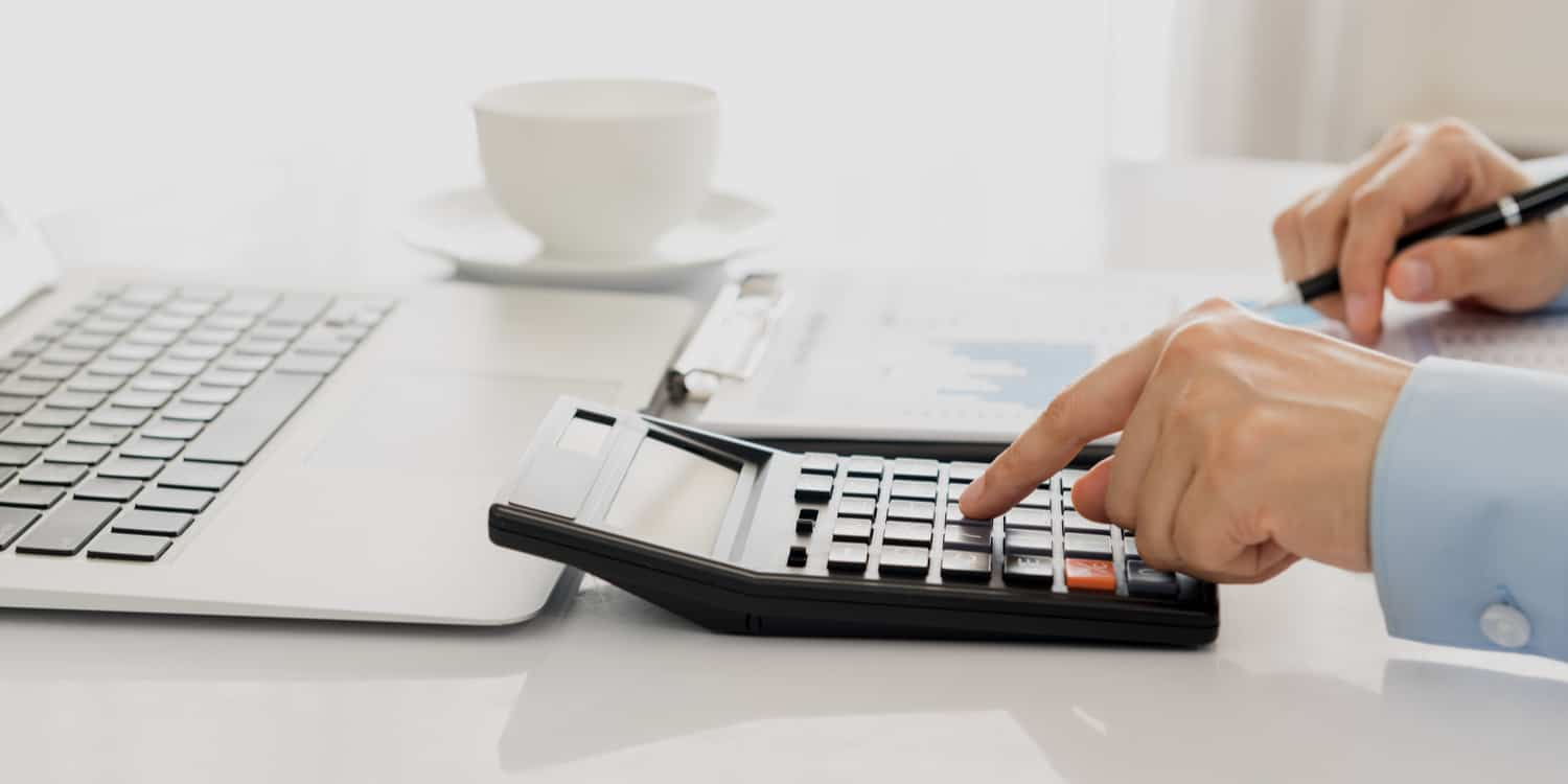 A business person working on company accounts and using a calculator.