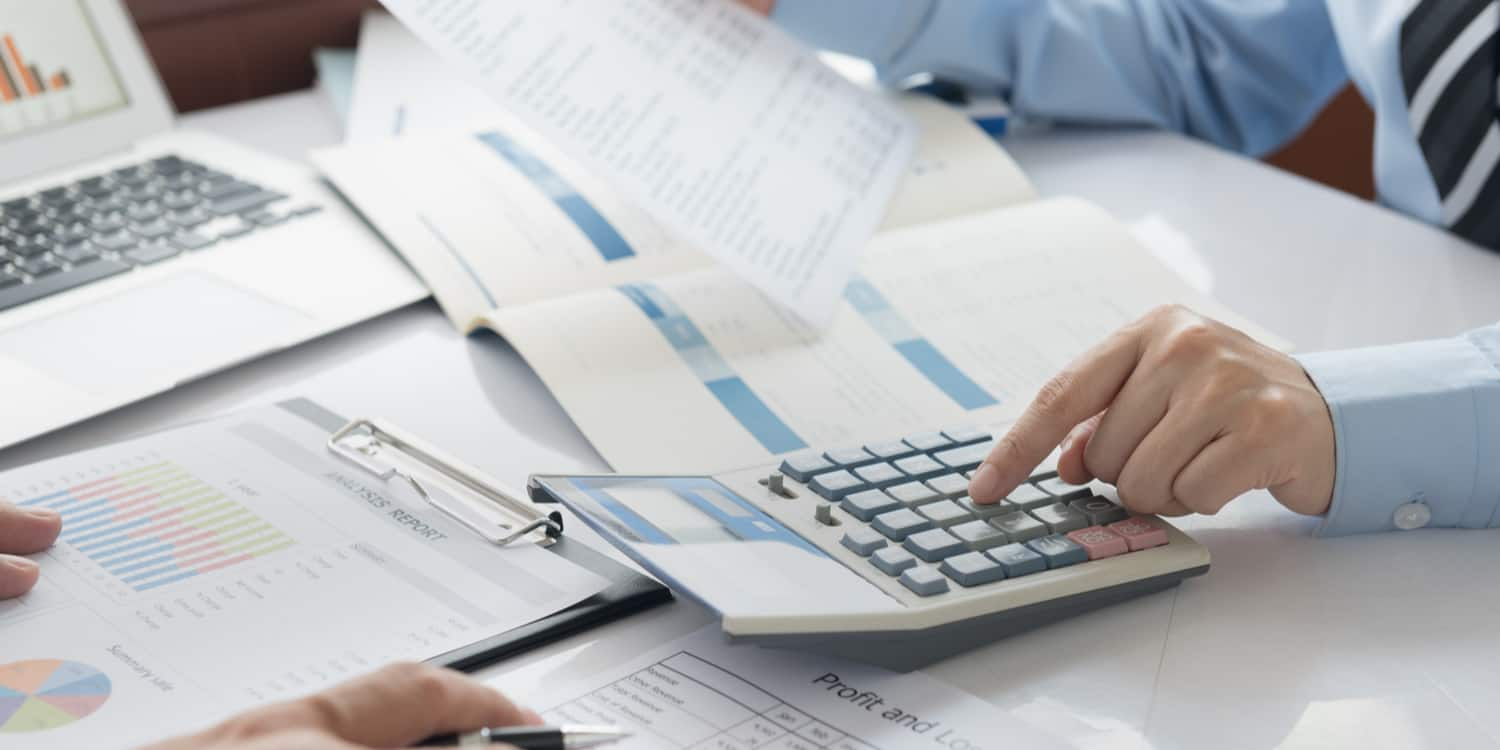 Business person working with a calculator with annual accounts documents on desktop.