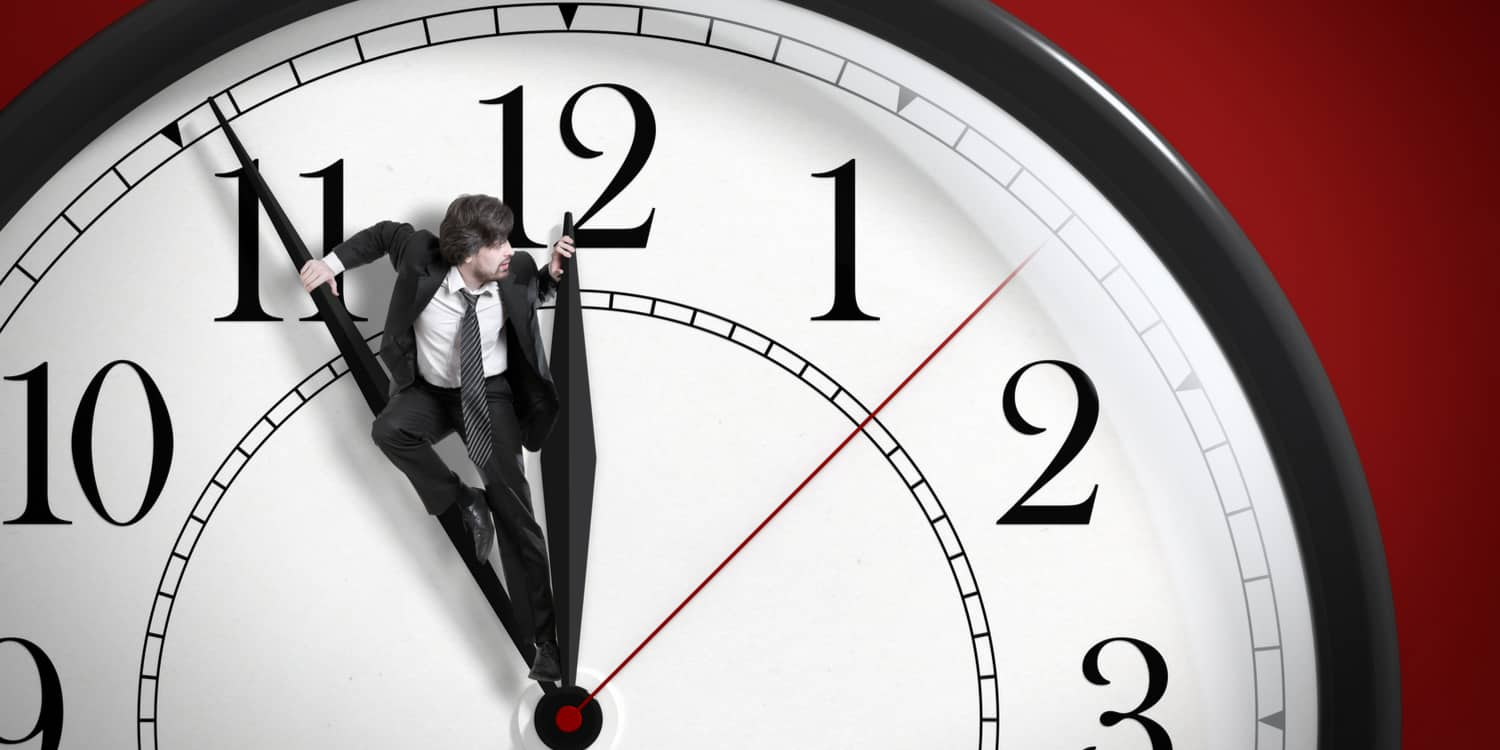 Business man standing on the hands of a clock trying to stop time.