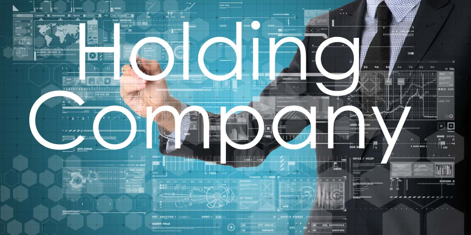"Business person working on full-size interactive screen with the words ""Holding Company"" displayed."