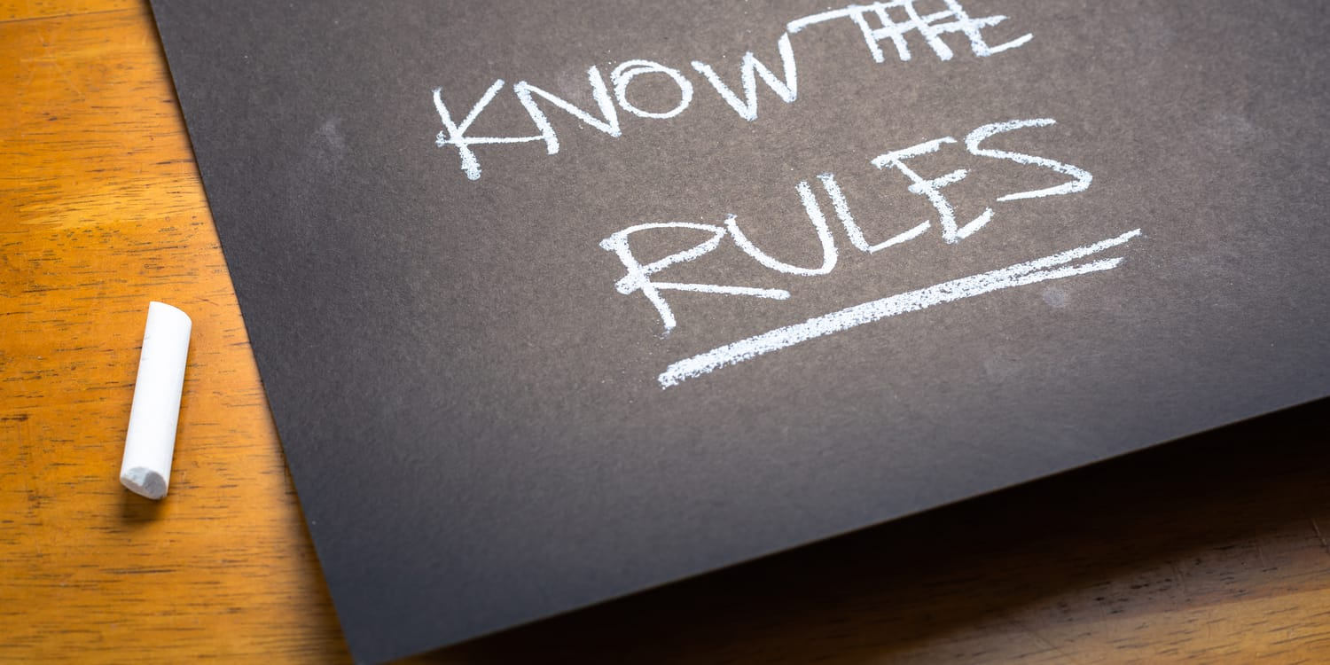 The words 'KNOW THE RULES' written in white chalk on a blackboard, illustrating the concept of choosing a company name