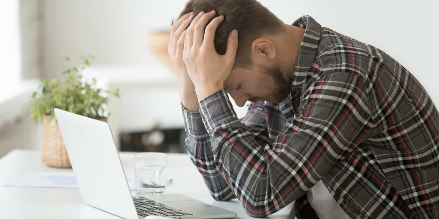 Young man with beard and checked shirt, sitting at laptop with head in hands, having lost his company's WebFiling authentication code.