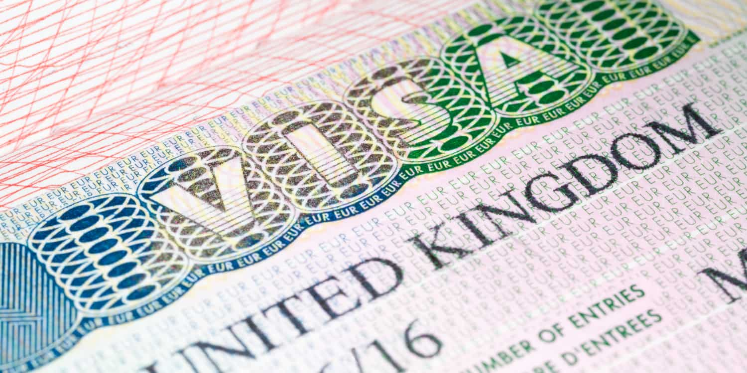Image of a page of a passport with a UK visa attached.