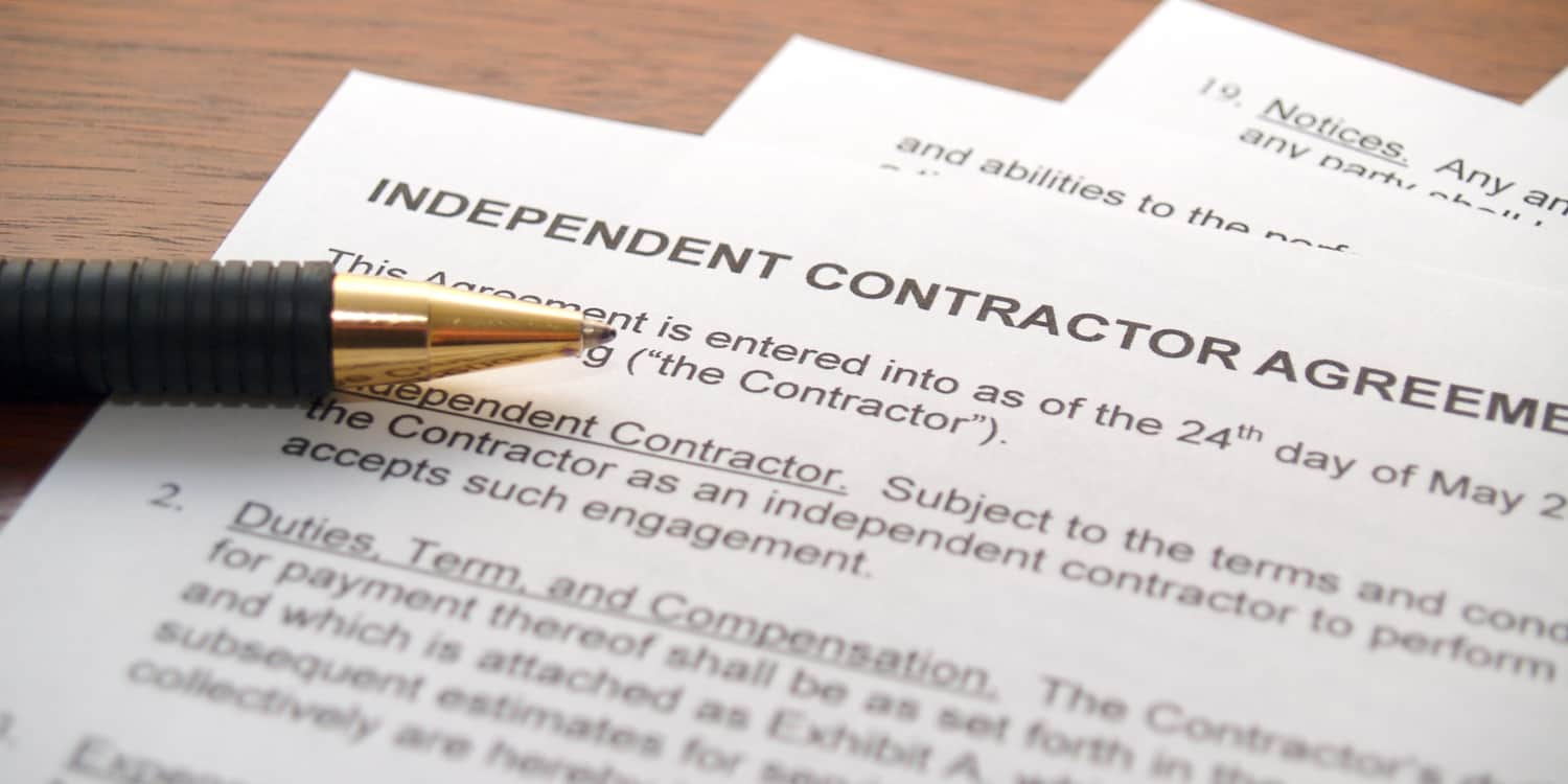 Independent Contractor Agreement lying on desktop with pen.