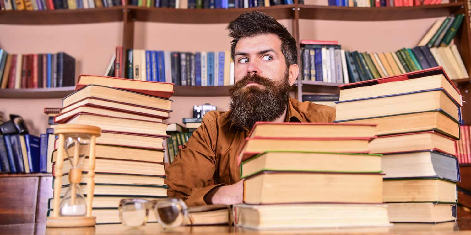 Young man with beard, sitting at a desk and surrounded by stacks of books.