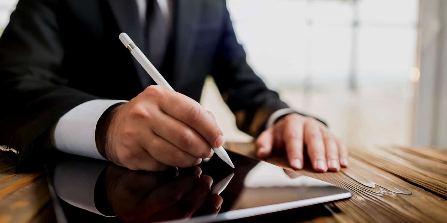 Businessman sitting at desk signing a document on an iPad using a light pen - illustrating the electronic signature concept.