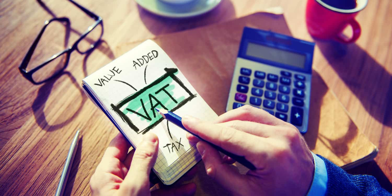 "Image of someone holding a notepad over a desk, with the words ""VAT"" and ""Value Added Tax"" written on the front, illustrating the process of deciding whether VAT registration is right for your business."