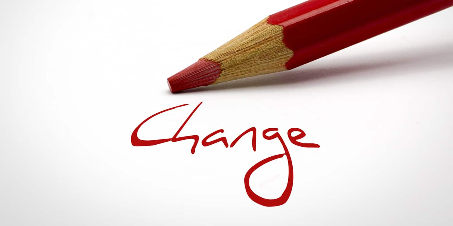 The word 'Change' written in red on white paper with red pencil in background.