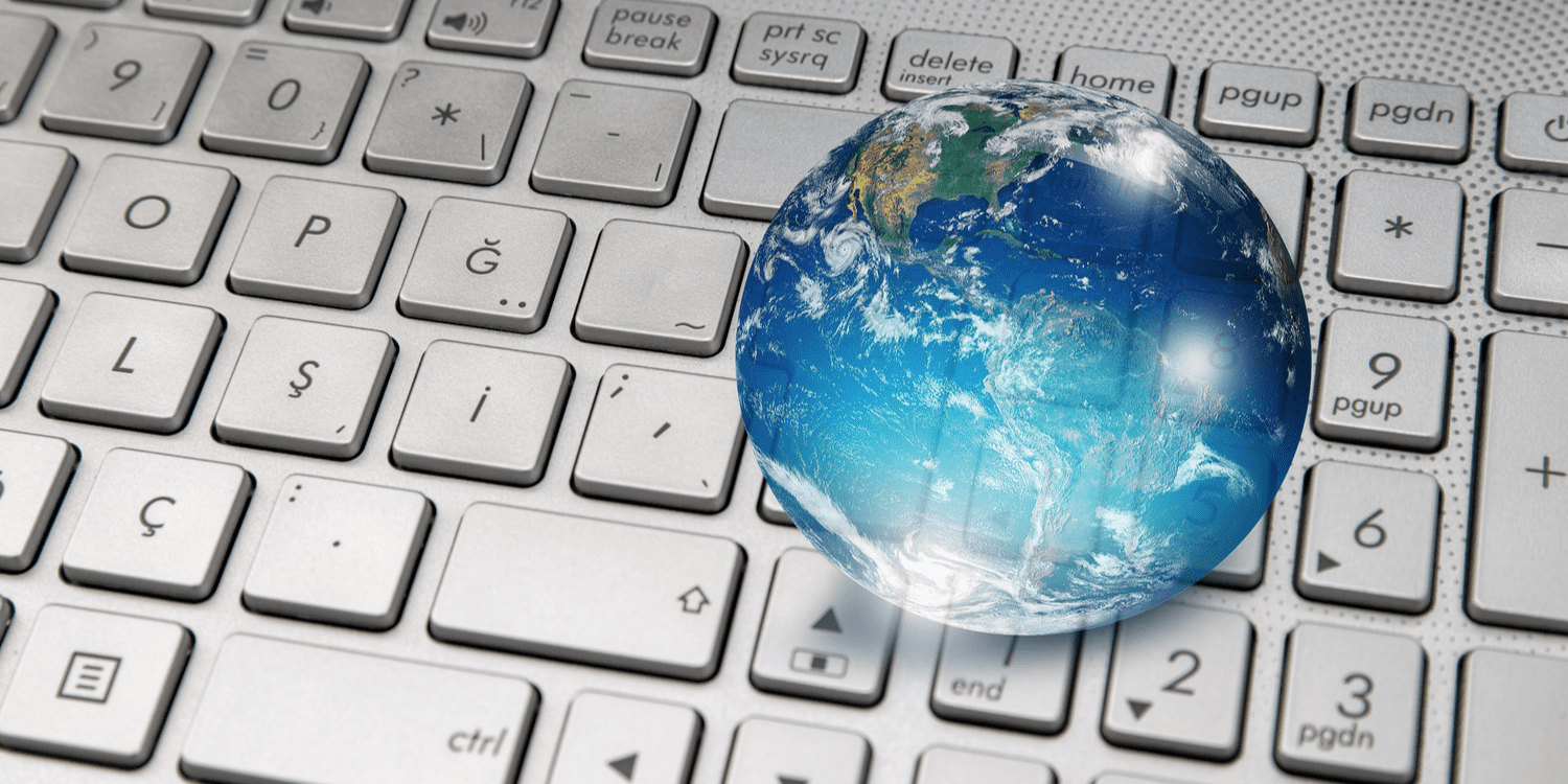 A glass globe sitting on top of a keyboard, demonstrating the concept of global business.