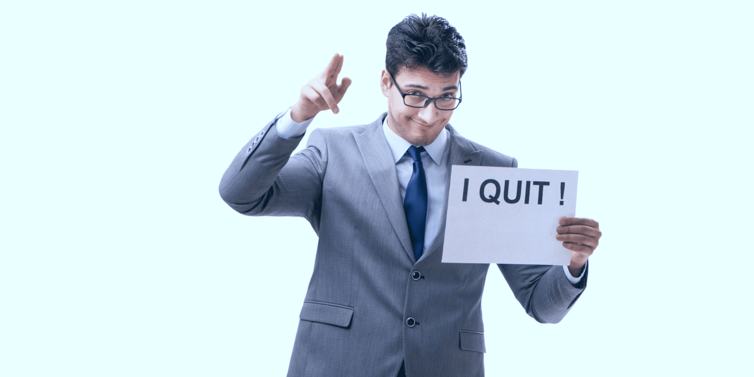 Company director in light grey suit with white shirt and dark blue tie, holding up a sign saying 'I QUIT'.
