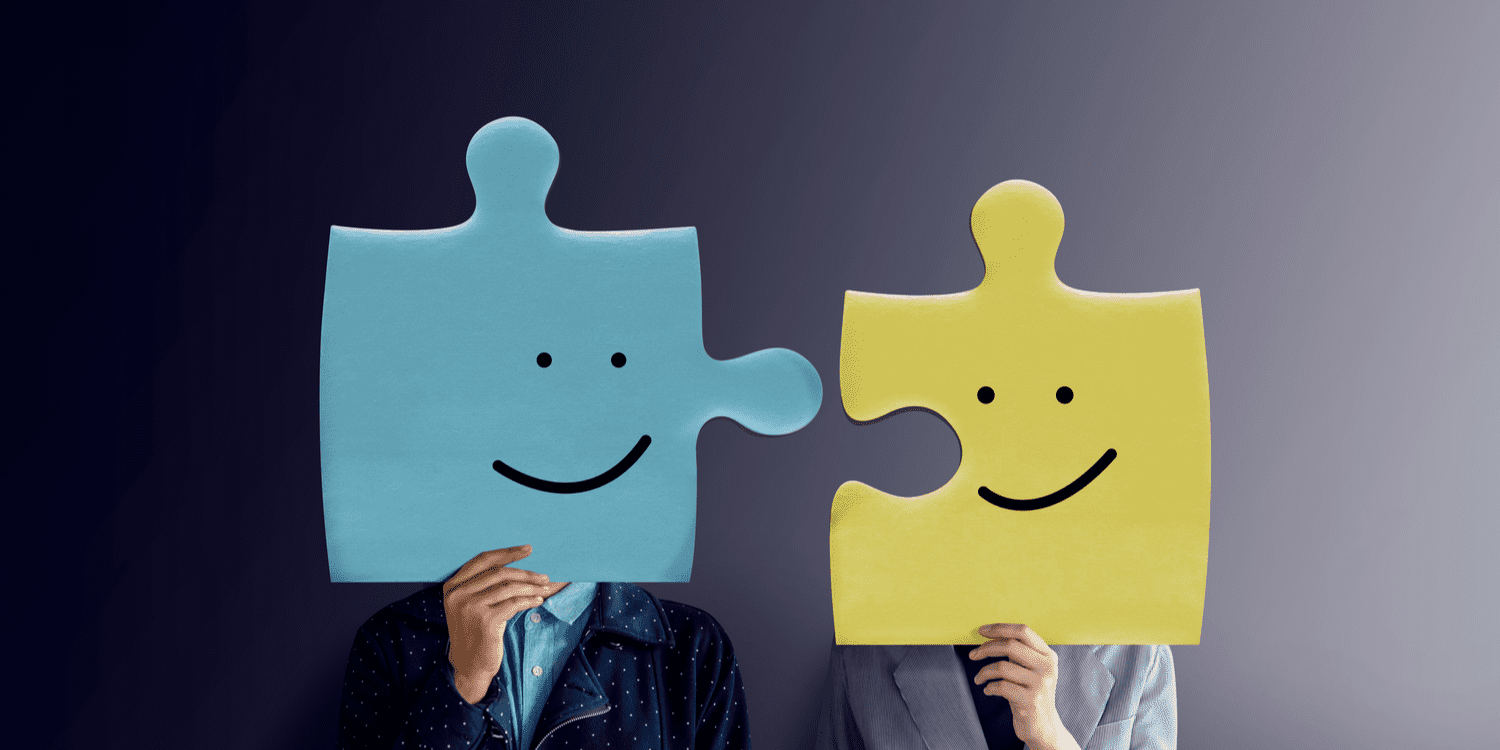Portrait of two people with happy face emotion on jigsaw puzzles, illustrating the business partnership concept.