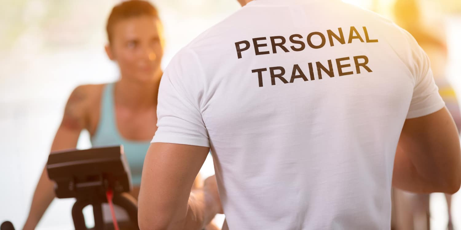Personal trainer in white t-shirt on weights lifting training with client
