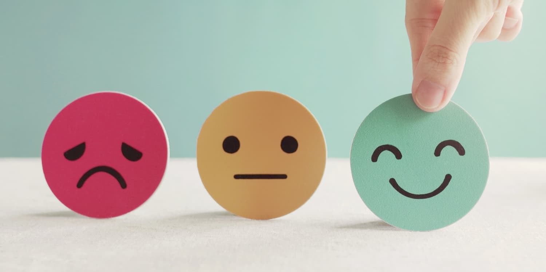Hand choosing happy smile face paper cut, illustrating mental health assessment concept.